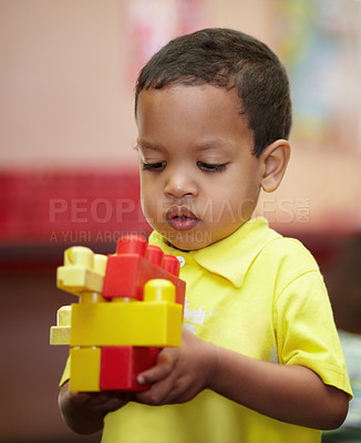 Buy stock photo A little ethnic boy concentrating on his plastic blocks in his pre-school class