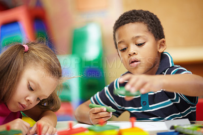 Buy stock photo Pre-school ethnic boy and girl scribbling and drawing with multi-coloured crayons in pre-school classroom