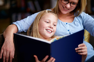 Buy stock photo A cute young girl sitting next to her mother while they read a book