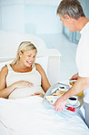 Relaxed pregnant woman in bed being served breakfast