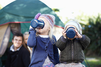 Buy stock photo Loving parents watching their children drinking from mugs while out camping