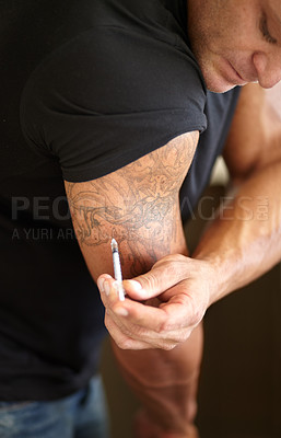 Buy stock photo Closeup of a muscular man injecting himself with steroids