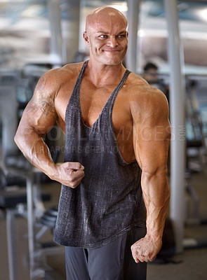 Buy stock photo A muscular bodybuilder flexing his muscles while standing in the gym