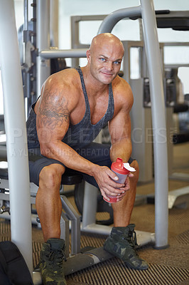 Buy stock photo Portrait of a male bodybuilder holding a protein shake while sitting on a weight bench at the gym
