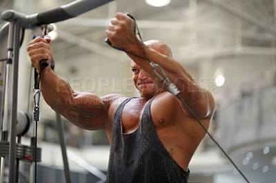 Buy stock photo A male bodybuilder using exercise equipment to train at the gym