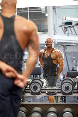 Buy stock photo A muscular bodybuilder flexing his muscles while watching his reflection in the mirror