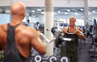 Buy stock photo Shot of a male bodybuilder looking in the mirror while lifting weights at the gym