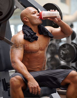 Buy stock photo Shot of a male bodybuilder drinking a protein shake while sitting on a weight bench at the gym