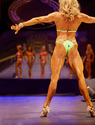 Buy stock photo Rearview of a female bodybuilding contestant flexing for the judges