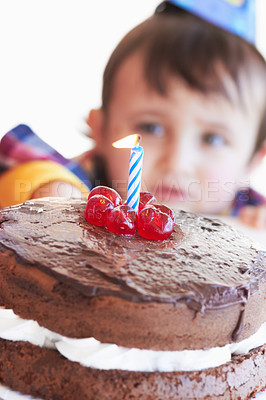 Buy stock photo A birthday cake with one candle with the birthday boy in the background