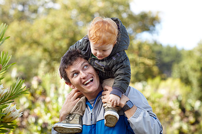 Buy stock photo A young father carrying his young son on his shoulders