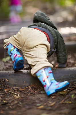 Buy stock photo Rearview of a young boy crawling in the dirt wearing gumboots