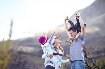Buy stock photo A young family with the children on their parent's shoulders while out hiking together