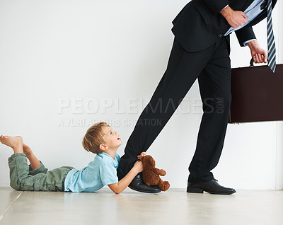 Buy stock photo A young boy holding onto his dad's leg to try and stop him from leaving to work