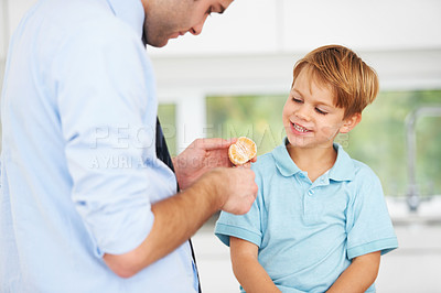 Buy stock photo A young father giving half of an orange to his little boy