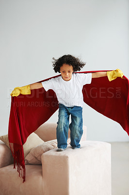 Buy stock photo A cute young boy pretend to fly his lounge sofa holding a blanket like a superhero's cape