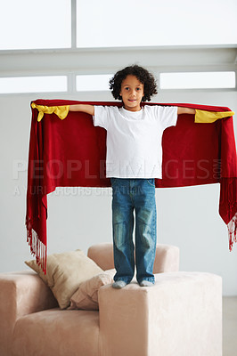 Buy stock photo Portrait of a cute young boy standing on the couch holding a blanket as a cape