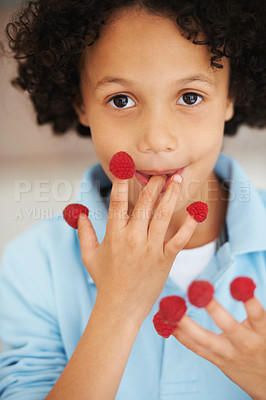 Buy stock photo Portrait of a cute young boy with raspberries on his fingers