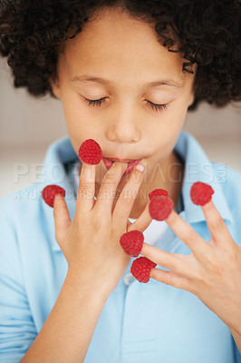 Buy stock photo A cute young boy eating raspberries off his fingers with his eyes closed