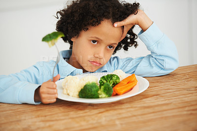 Buy stock photo Shot of an unimpressed-looking little boy sitting in front of a plate of vegetables