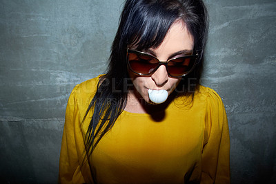 Buy stock photo A young woman wearing sunglasses and chewing gum