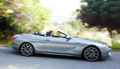 Buy stock photo A young man driving a silver sportscar
