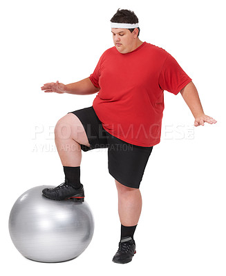 Buy stock photo An overweight young man balancing one foot on a swiss ball