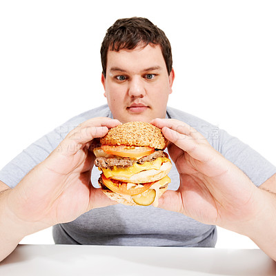 Buy stock photo A young obese man looking yearningly at the burger he is holding