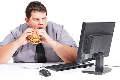 Buy stock photo A young man eating his lunch at his desk at work while staring with mouth agape at his monitor - unhealthy eating habits