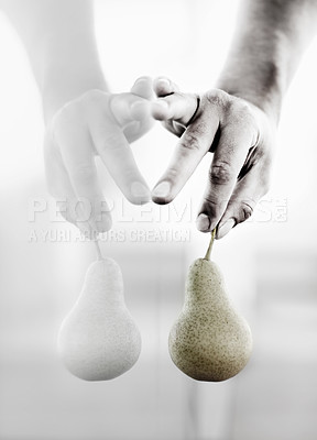 Buy stock photo Closeup of a hand holding a pear by it's stem against a reflective surface