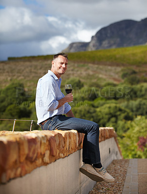 Buy stock photo Portrait of a mature man sitting on wall and enjoying a glass of red wine