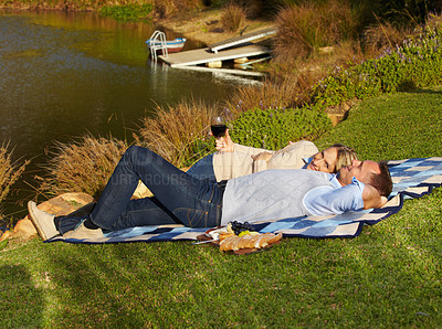 Buy stock photo A happy mature couple lying on a picnic blanket and enjoying a glass of wine
