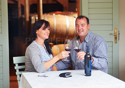 Buy stock photo A happy mature couple toasting with some red wine while sitting at a table on a wine cellar
