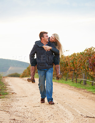 Buy stock photo A young man carrying his girlfriend on his back while taking a walk on a vineyard