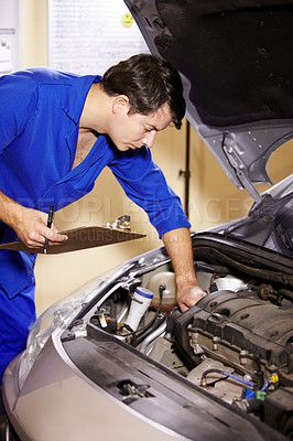 Buy stock photo A male mechanic holding a clipboard while working on the motor of a car