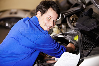 Buy stock photo Portrait of a male mechanic working on the engine of a car with some papers next to him