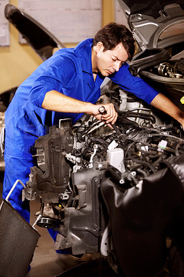 Buy stock photo A male mechanic working with a spanner on the motor of a car