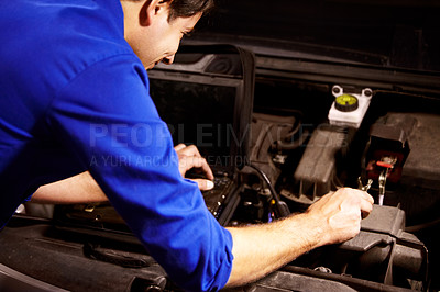 Buy stock photo A male mechanic running diagnostics on the electronics of a car using a laptop