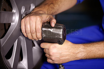 Buy stock photo Cropped image of a male mechanic's hands working on the wheel of a car