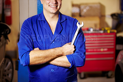 Buy stock photo Cropped image of a male mechanic standing confidently while holding a spanner