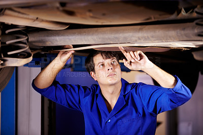 Buy stock photo A young male mechanic looking at the steering rack under a car