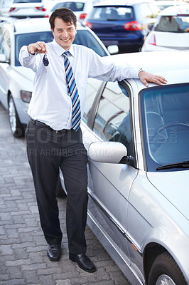 Buy stock photo A happy car salesman handing you the keys to your new car
