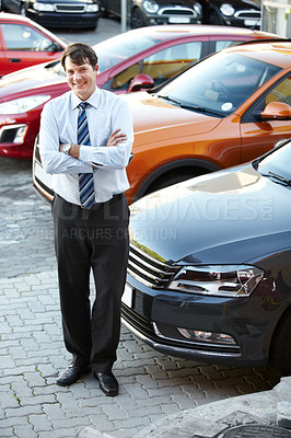 Buy stock photo A man standing confidently and smiling in the lot of his dealership