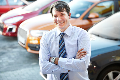 Buy stock photo A man smiling confidently while standing in the lot of his dealership
