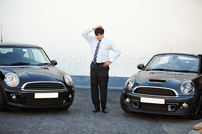 Buy stock photo A man scratching his head while he decides whether or not to go for the convertable