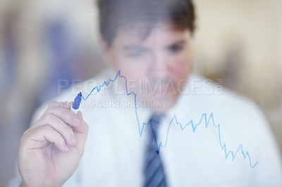 Buy stock photo Shot of a businessman writing on a clear wall with a blue pen