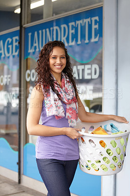 Buy stock photo Portrait of a young attractive woman carrying her laundry to the laundromat