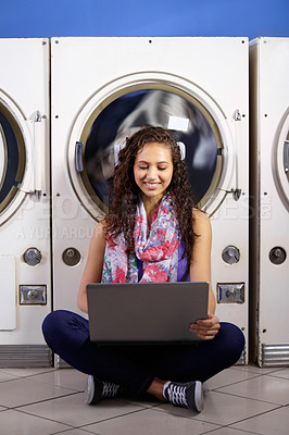 Buy stock photo A young attractive woman sitting with her laptop on the floor of the laundromat