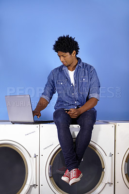 Buy stock photo A handsome young man sitting on top of a washing machine with his laptop and cellphone at the laundromat