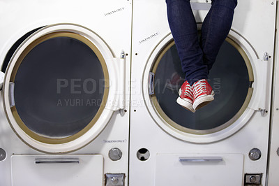 Buy stock photo Cropped image a man's legs as he sits on a washing machine at the laundromat